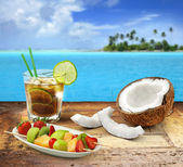 Cuba libre and tropical fruit on a wooden table in a polynesian seascape — Stock Photo