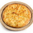 Whole focaccia in a straw tray over white — Stock Photo
