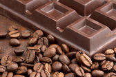 Chocolate bar and coffee beans on wooden table — Stock Photo