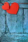 Duas placas em forma de coração pendurado numa prancha azul — Fotografia Stock