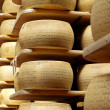 Stock Photo: Wheels of cheese on racks of maturing storehouse
