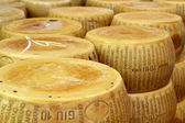 Close up of a heap of wheels of seasoned parmesan — Stock Photo
