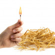 Stock Photo: Hand holding burning matchstick near haystack