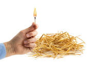 Hand holding a burning matchstick near a haystack — Stock Photo