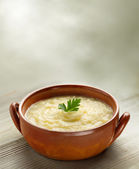 Steaming bowl of potato soup on wooden table — Stock Photo