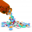Mixed pills spilling out of a glass bottle — Stock Photo #40682151