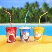 Fresh fruit smoothies on a tropical beach — Stock Photo