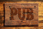 Rustic pub sign on wooden wall — Stock Photo