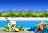 Fresh mojito cocktail, starfish and sarong in a tropical landscape — Stock Photo