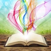 Open book with colored smoke swirls and twirls — Stock Photo