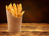 French fries in a paper basket on wooden table — Stock Photo