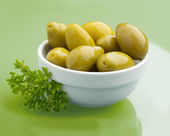 Green olives in a bowl on glass table — Stock Photo