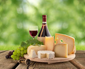 Cheese board, grape and red wine on wooden table — Stock Photo