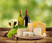 Cheeseboard, grape and wine on wooden table in countryside — Stock Photo