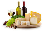 Cheeseboard, grapes, wineglasses and wine bottles — Stock Photo