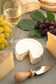 Assorted cheese, wineglass and bread on wooden table — Stock Photo