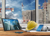 Tablet, smartphone, safety helmet and blueprints in construction site — Stock Photo
