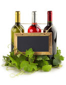 Blackboard hanging on wine bottles and grapevine leaves — Stock Photo