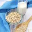Oat flakes in bowl and milk — Stock Photo