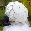 Bride and groom under an umbrella — Stock Photo