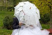 Bride and groom under an umbrella — Stock Photo
