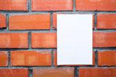 Folha de papel sobre o fundo de tijolos em branco — Fotografia Stock