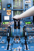 Hand on top of an Airplane cockpit's thrust levers. — Stock Photo