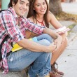Young students sitting in the street holding books. — Stock Photo #24580997