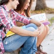 Young students sitting in the street holding books. — Stock Photo #24581003