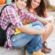 Young students sitting in the street holding books. — Stock Photo #24581009