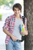 Young man holding books on the street — Stock Photo
