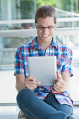 Young smiley male using tablet pc wearing reading glasses — Stock Photo