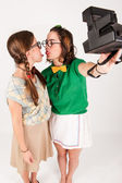 Young nerdy girls taking a selfie with instant camera. — Stock Photo