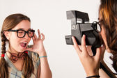 Young nerdy girls using instant camera. — Stock Photo