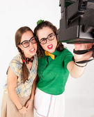 Young nerdy girls taking a selfie with instant camera. — Stockfoto