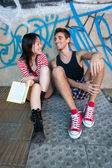 Young multi-ethnic couple reading a book. — Stock Photo