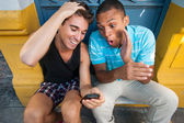 Young males having fun with a cellphone. — Стоковое фото