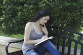 Girl writes in park — Stock Photo
