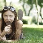 Girl eating ice cream on grass — Stock Photo