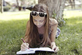 Girl writes something in notebook — Stock Photo