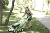 Girl with lawn mower — Stock Photo