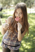 Happy girl eating lollipop — Photo