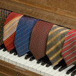 Neckties over a piano — Stock Photo