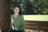 Young woman sitting in park — Stok fotoğraf