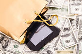 Gold gift bag with a Tablet and dollars — Stock Photo