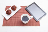 Chocolate chips Muffins with a cup of coffee and a tablet PC — Stock Photo
