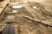 Broken road surface with water — Stock Photo