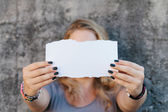 Teenage girl holding sheet of paper — Stock Photo