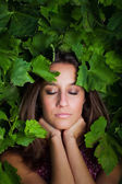Close-up portrait of young beautiful women in leafs — Stock Photo