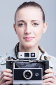 Woman holding up a camera about to take a photo. Focus on eye — Stock Photo